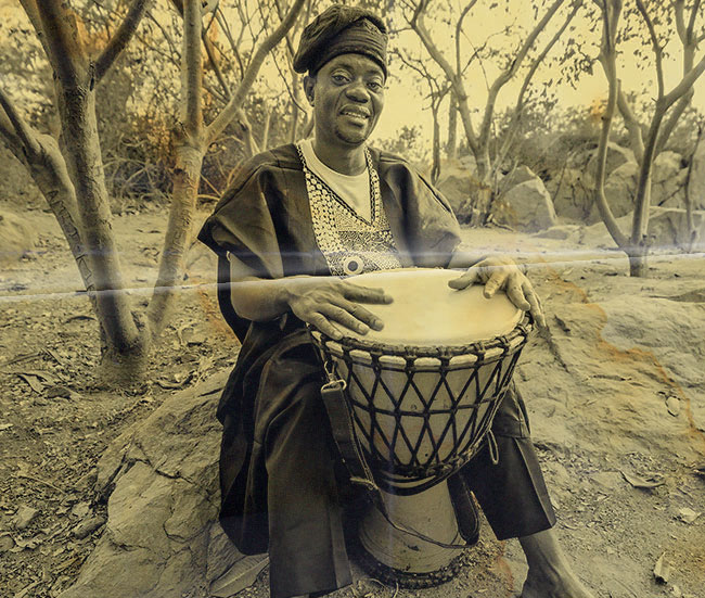 Old black and white photo of a djembe player